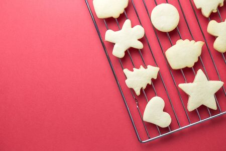 Flat lay of christmas cookies on oven grate against red background minimal creative holiday and food concept. Space for copy.