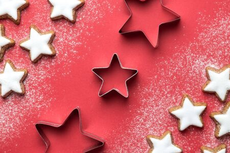 Flat lay of christmas star cookies with cutters on red background minimal creative concept. Banco de Imagens