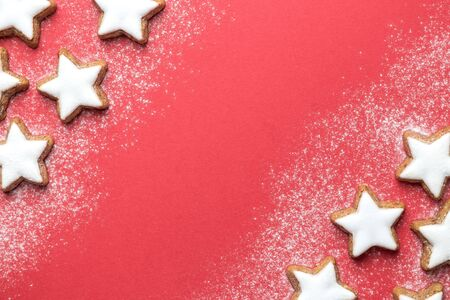 Flat lay of christmas star cookies on red background minimal creative concept.