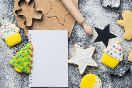 Flat lay of making Christmas cookies concept with blank paper notebook for recipe on table. Space for copy. Banco de Imagens