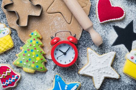 Flat lay of time for Christmas cookies preparation concept made of cutters, dough, rolling pin, biscuits with colorful icing and alarm clock on table. Banco de Imagens