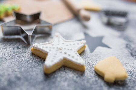 Close up of star cookie decorated with white icing with cutters, dough and rolling pin in the background on table, christmas dessert preparation concept.