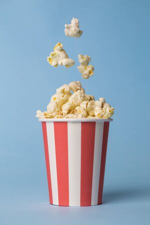 Popcorn falling into paper cup against pastel blue background minimal creative food concept.