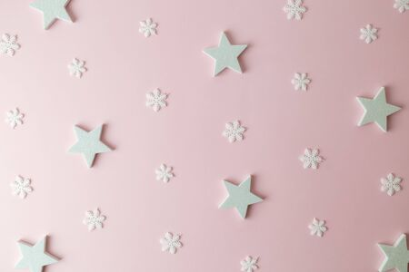 Pattern made of white stars and snowflakes on pastel pink background minimal creative christmas holiday and winter concept.