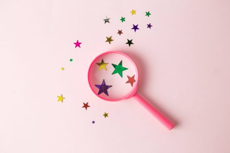Flat lay of magnifying glass with colorful stars on pastel background minimal creative search concept.