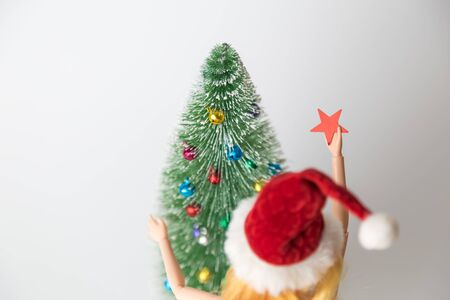 Rear view of girl doll in Santa hat holding star decoration next to fir tree and preparing for Christmas home decoration minimal creative holiday concept.