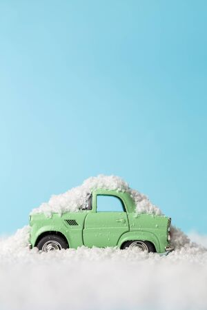 Close up of car toy covered with snow after winter storm abstract on pastel blue background.