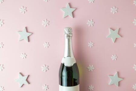 Top view of champagne bottle against pattern background made of stars and snowflakes. Celebration concept.