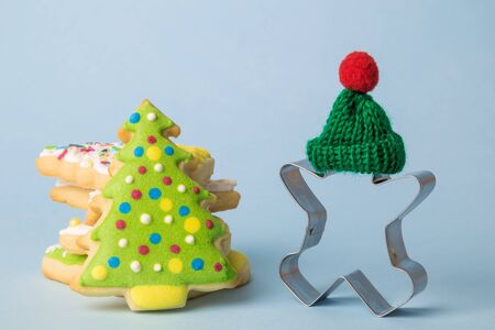 Gingerbread man cookie cutter wearing green hat and holiday cookies with colorful icing on pastel blue background winter season and christmas food minimal creative concept. Banco de Imagens