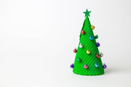 Christmas tree abstract made of ice cream cone and miniature multicolored baubles with star on white. Space for copy.