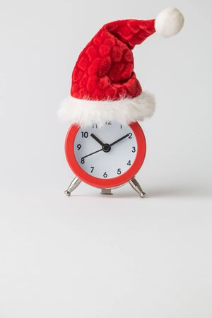 Small analog clock with Santa Claus hat abstract isolated on white. Winter season and christmas time concept.