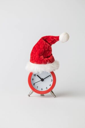 Red alarm clock wearing Santa hat against white background minimal creative christmas holiday concept. Space for copy.
