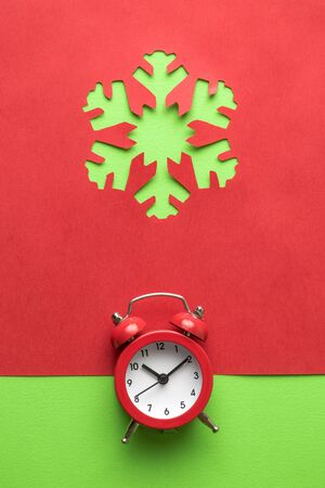 Snowflake made of paper and small alarm clock minimal creative winter holidays concept.