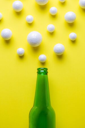 Flat lay of green beer bottle and bubbles made of styrofoam balls against yellow background minimal creative drink concept.