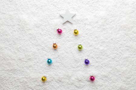 Flat lay of colorful baubles and star in form of christmas tree on snow minimal holiday creative concept. Banco de Imagens