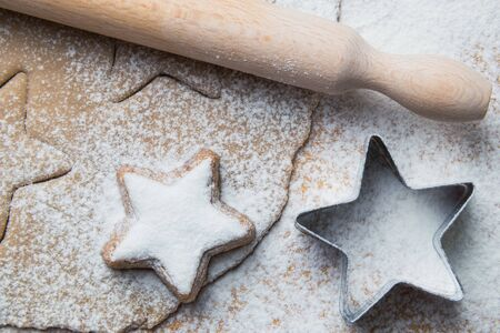 Dough with other Christmas baking ingredients on the table. Star shape cookies preparation.
