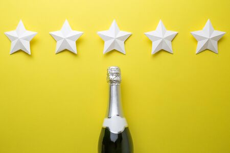 Flat lay of champagne bottle and five paper stars on yellow background minimal creative concept.