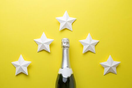 Top quality champagne wine abstract made of bottle and origami stars isolated on yellow.