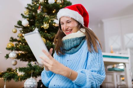 Young cheerful pregnant woman holding tablet device against christmas tree at home.