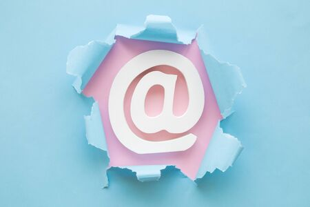 Email symbol with pastel blue torn paper on pink background minimal creative concept.