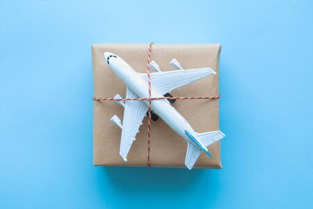Cardboard delivery box with small airplane abstract on blue.