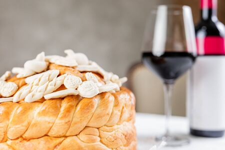 Bottle and glass of wine and Orthodox church bread with decoration on table at restaurant or home.