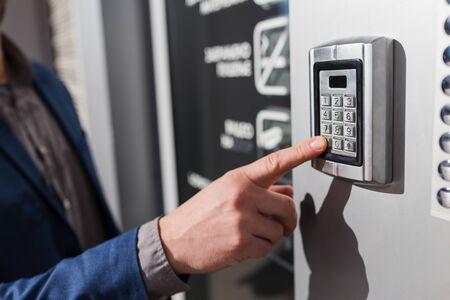 Gros plan sur une main d'homme d'affaires entrant le code du système de sécurité.