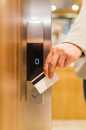 Close up of businessman hand holding key card to unlock elevator access, corporate building security concept. Imagens