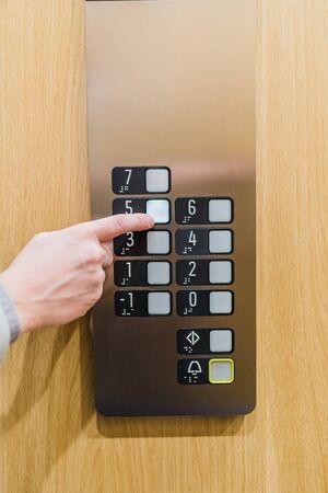 Forefinger pressing fifth floor button in the elevator. Space for copy. Banque d'images