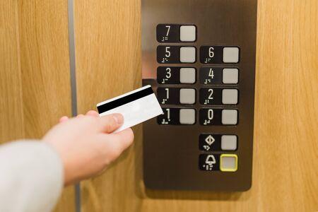 Businessman hand holding key card to unlock elevator floor.
