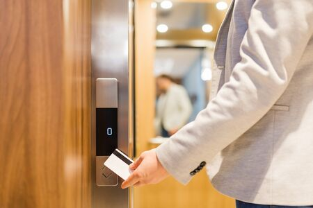 Man holding key card on sensor to open elevator door in modern building or hotel.