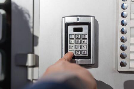 Man hand pressing the security code combination to unlock the door