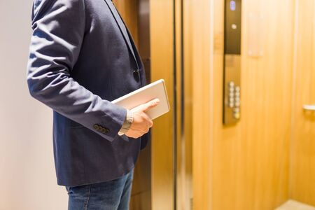 Close up of businessman with tablet device in front of modern elevator. Business and office building meeting concept.