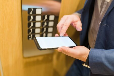 Close up of businessman using blank screen smartphone next to elevator control panel. Business and office building meeting concept. Stock Photo