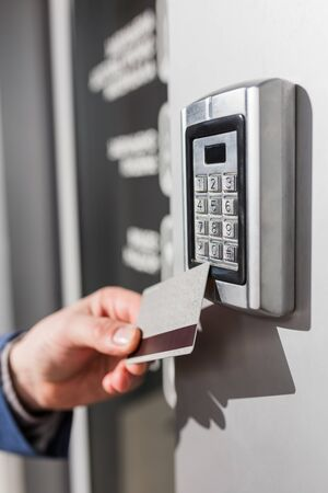 Man scanning security key card on electric lock to entry private building.