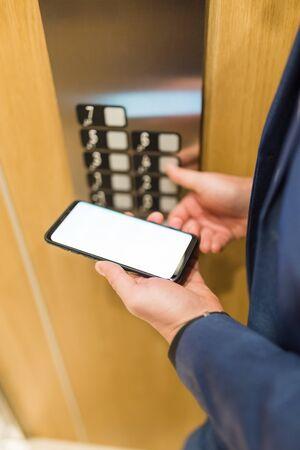 空白の画面のスマートフォンを使用して、エレベーターボタンを押してビジネスマンのクローズアップ。ビジネスとオフィスビル会議のコンセプト。