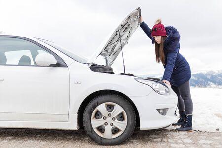 Woman checking car engine problem. Car breakdown road assistance concept. Winter scene.