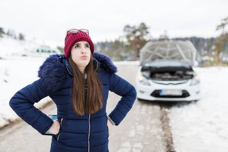 Stressed woman and broken car with opened hood in the background. Road trip problems and assistance concepts.