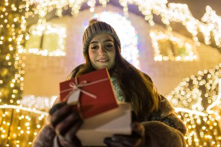Beautiful young woman opening gift box outdoors. Christmas new year surprise concept.