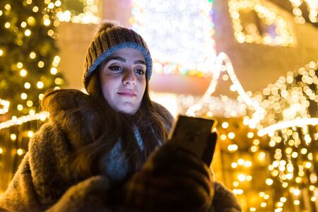 Portrait of young woman using smart phone against house with christmas lights decoration.