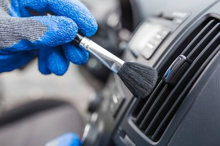 Worker cleaning automobile air conditioner vent grill with brush, closeup. Car wash service