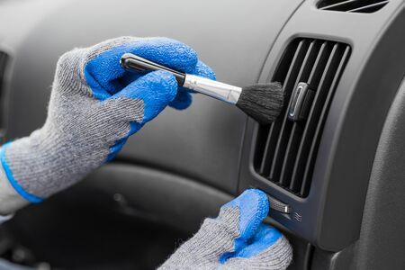 Man hands wearing protective gloves using cleaning brush and removing dust from car air conditioning vent grill. Car detailing or valeting concept.