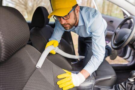 Man worker using vacuum cleaner in car