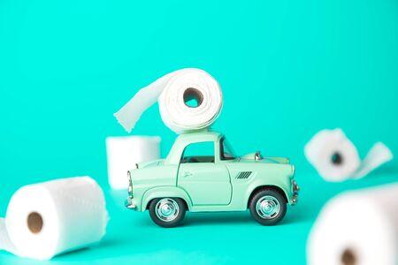 Small car with toilet paper corona virus pandemic panic minimal creative concept. Stockfoto