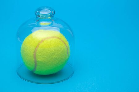 Tennis ball under glass cover isolation covid-19 abstract. Banco de Imagens