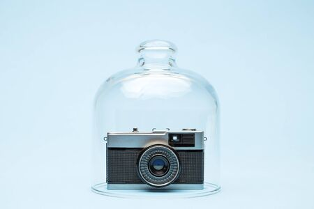 Retro film photo camera in quarantine minimal creative coronavirus travel or celebration event cancellation concept.