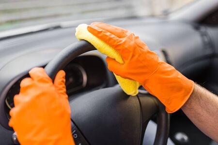 Hands in protective gloves cleaning car steering wheel with microfiber cloth.