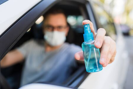 Driver wearing protective medical mask holding spray bottle of disinfectant alcohol.