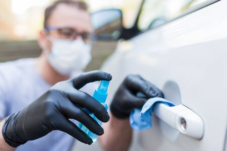 Driver with face mask wearing rubber protective gloves wiping and spraying car door handle. Virus and bacteria prevention concept.
