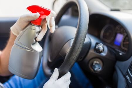 Driver wearing protective gloves and spraying disinfectant on car steering wheel to prevent infection.